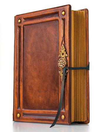 Vintage book in warm brown leather with gilded paper edges and metal buckle stand up to the table Archivio Fotografico