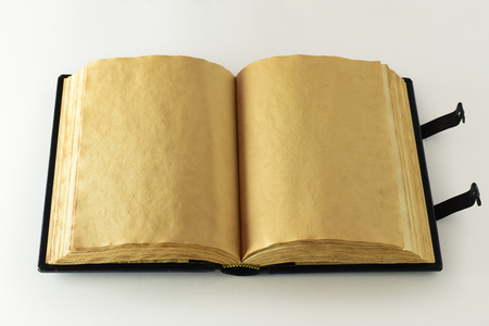 Opened book with aged yellow page, clasps and wavy paper edges. Light source from the left side.