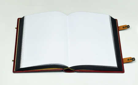 Opened book with white page, clasps and painted paper edges in black color. Light source from the top.