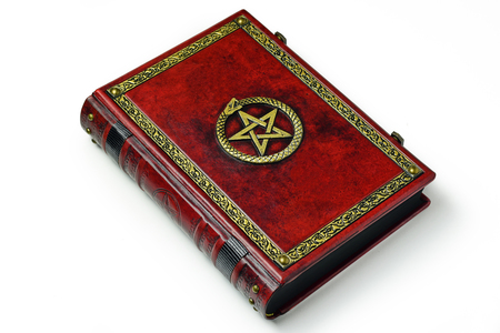 Red leather book with gilded frame, pentagram and metal clasps. Isolated book laying to the table, captured from the left side. Archivio Fotografico