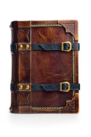 Aged brown leather book cover with two black belts for keeping the book closed. The book back cover is captured isolated while stand up on the table.