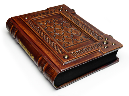 Large leather bound book with Latin text Memento Mori engraved several times as a frame - laying on the table, left side. English translation of the Latin text is: Remember that you have to die