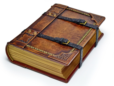 Aged leather book with straps and gilded paper edges - laying on the table isolated