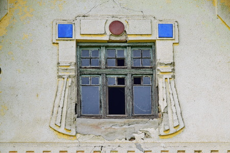 Aged window with unusual facade decoration on the old German house