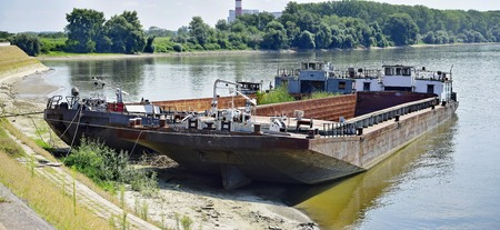 Two abandoned ships left tight on the river shore