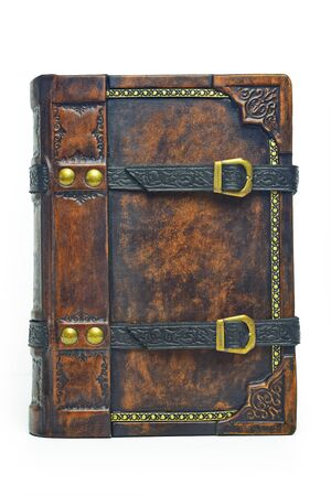 Aged brown leather book cover the gilded frame and with two black belts for keeping the book closed. The book is captured isolated while stand up on the table. Archivio Fotografico