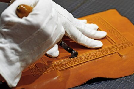 Embossing the frame with hot hand tool into the leather book cover while caring the gloves on hands Archivio Fotografico