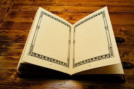 Opened book on the half, lay down to the  dark brown wooden table. Yellowish parchment pages has the frame.