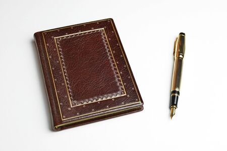Brown leather journal with the posted golden fountain pen on the side Archivio Fotografico