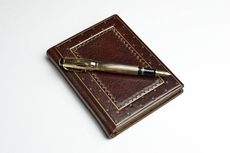 Brown leather journal with the posted golden fountain pen over the book cover
