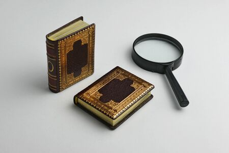 Two miniature leather books with the magnifying glass