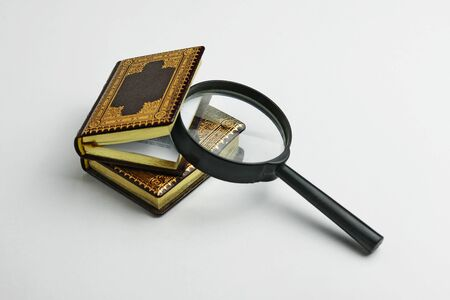 Two miniature leather books with the magnifying glass placed between pages