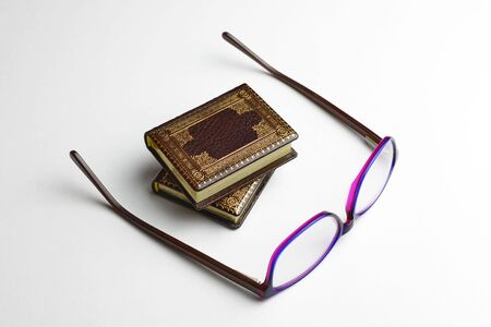 Two miniature leather books with the glasses placed on the side of books