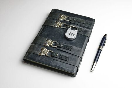 Aged black leather journal locked with the padlock. Black pen lay down on the book side