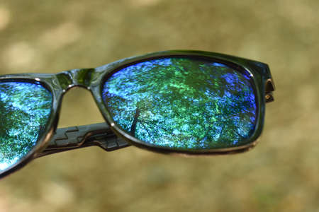 Green trees and blue sky reflection on blue lens glasses