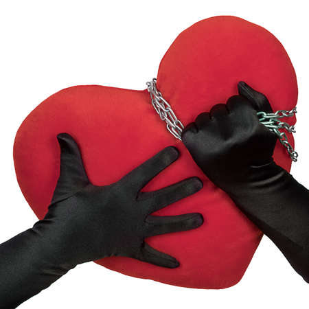 Big red heart in hands with chains