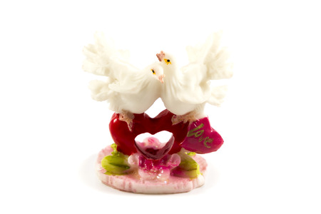 Ceramic figurine of two pigeon sitting opposite one another on the heart with the word love photo