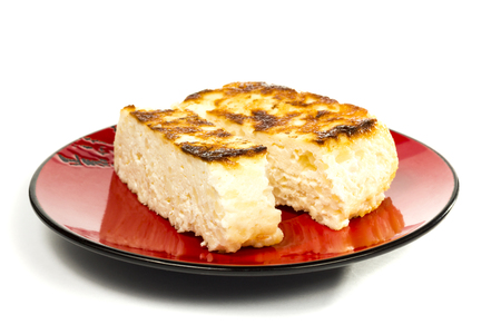 Сheese casserole on a red plate to cut off a piece on a white background photo