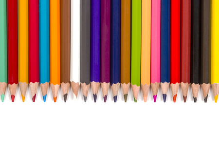 disposed: A set of colored pencils disposed face down next to each other on a white background