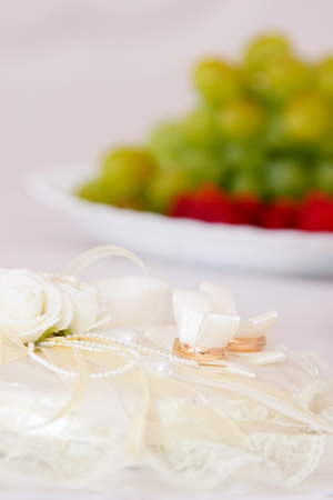 Gold wedding rings on wedding white cushion in the background plate with fruits photo