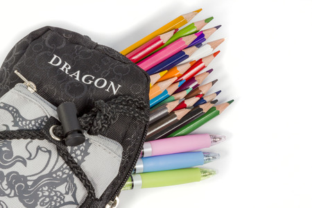 protrude: Black school pencil box with an inscription Dragon from which protrude pencils and pens