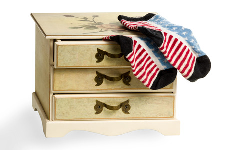 protrude: Children dresser with an open top drawer from which protrude socks as the American flag isolated on white background