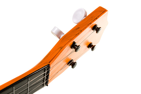 solo form: Fretboard child plastic four-stringed guitar red color closeup isolated on white background