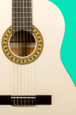 Detail of classic white acoustic wooden guitar with strings and soundboard socket isolated on green background photo