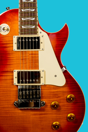 soundboard: Brown electric guitar closeup with white plate on the soundboard isolated on a blue background Stock Photo