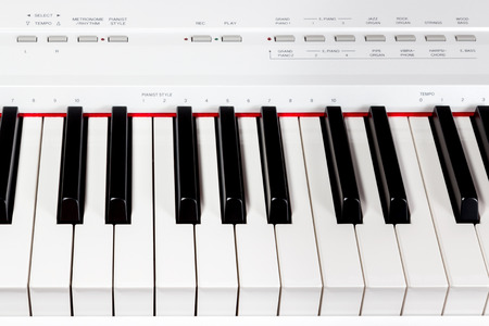 Keys of white electric music synthesizer with a set of buttons photo