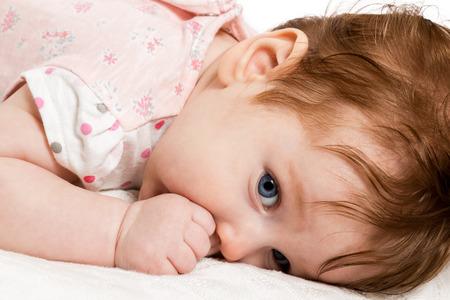 sucks: Beautiful baby lying on the bed and sucks his thumb