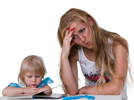Tired mom teach daughter reading a book at the table isolated on white background photo