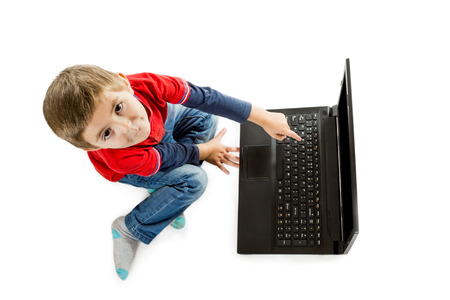 Little boy in red sweater and jeans sitting on floor and pointing to an open laptop top view isolated on white background photo
