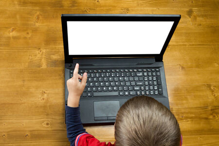 Little boy at the table pointing to an open laptop screen top view isolated on white background photo