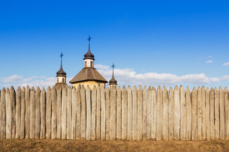 steeples: Wooden church with three steeples and crosses is behind a fence of logs against the sky