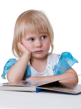 Little girl with blond hair leaned on his elbow and lost in thought before an open book isolated on white background photo