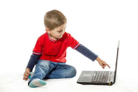Little boy in red sweater and jeans sitting on floor and pointing to an open laptop isolated on white background photo