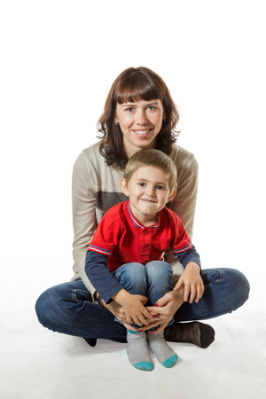 Smiling mother holding her son in her arms while sitting with him on the floor isolated on white background photo