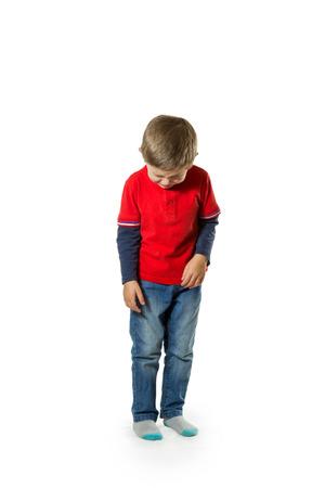 niño llorando: Niño pequeño en suéter rojo y jeans pie bajó la cabeza y llorando aislado en fondo blanco