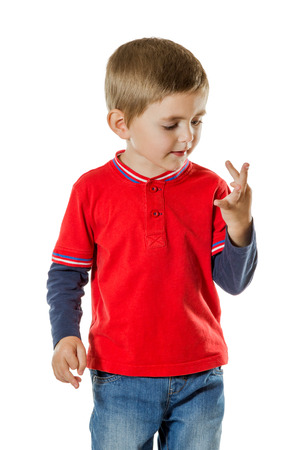 Little boy in a red sweater and blue jeans considers her fingers isolated on white background