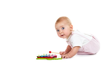 Baby playing music toy xylophone isolated on white background