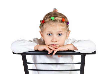 Portrait of girl with blue eyes on a chair isolated on white background photo