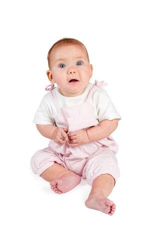 ojos azules: Bebé en una camiseta de color rosa y blanco monos se sienta con la boca abierta y mirando a cámara aislada sobre fondo blanco