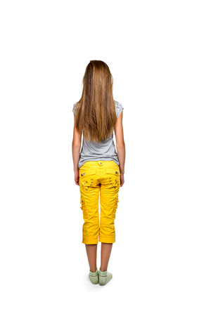Girl with long flowing hair in a gray shirt and yellow trousers standing back to camera isolated on white background photo