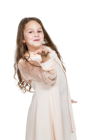 Little girl in a beige dress sends blowing a kiss to the camera isolated on a white background photo