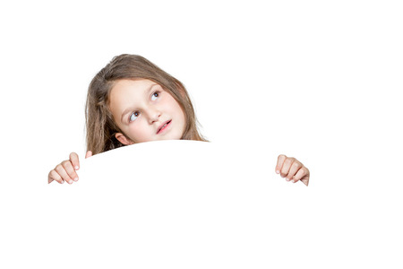 Little girl peeping from behind a round white panel isolated on white background