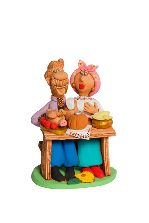 Clay statuette a husband and wife sit at a table with food isolated on white background photo