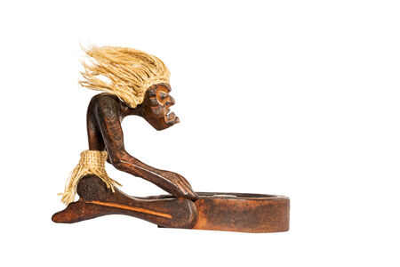 rite: Wooden figurine African shaman performs the rite before the trough isolated on a white background