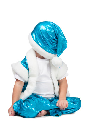 aslant: Kid in blue suit of Santa sitting on the floor and put his hat over his eyes isolated on white background