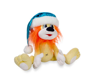 new year's cap: Seated toy yellow lion with an orange mane in blue santa hat isolated on white background